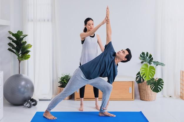 Azjatycka młoda para razem ćwiczyć i grać w jogę w domu