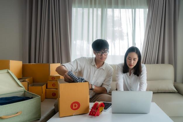 Azjatycka młoda para sprzedaje online za pośrednictwem komputera i pomaga zaznaczyć pole, aby wysłać pocztę w salonie w domu. małe przedsiębiorstwo rozpoczynające działalność jako przedsiębiorca lub niezależny przedsiębiorca
