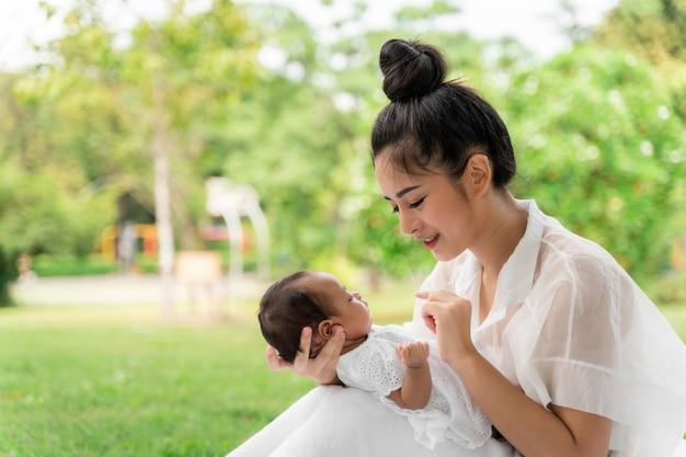 Azjatycka młoda piękna matka trzyma jej nowonarodzonego śpi i czuje z miłością i delikatnie dotyka następnie siedzi na zielonej trawie w parku