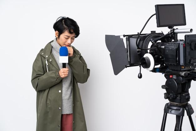 Azjatycka młoda piękna reporter kobieta nad biel ścianą