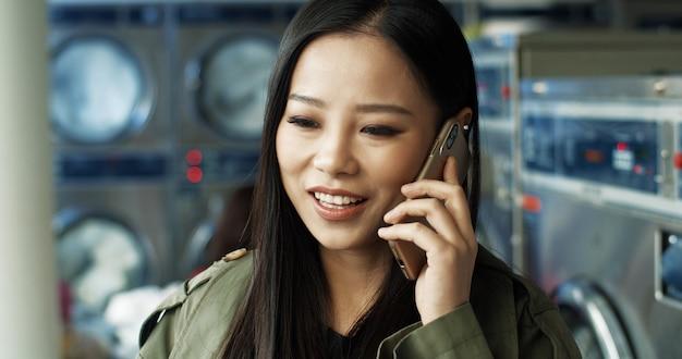 Azjatycka młoda piękna rozochocona dziewczyna ono uśmiecha się i opowiada na telefonie komórkowym w pralnianym usługowym pokoju. ładna kobieta mówi na telefon komórkowy, czekając na ubrania do prania w publicznej pralni