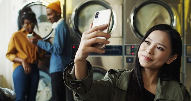 Azjatycka młoda piękna rozochocona dziewczyna ono uśmiecha się i pozuje smartphone kamera podczas gdy brać selfie fotografię w pralni. dosyć szczęśliwa kobieta robi selfie fotografiom z telefonem przy pralkami.