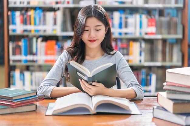 Azjatycka młoda studentka w garniturze czytająca książkę na drewnianym stole w bibliotece uniwersyteckiej