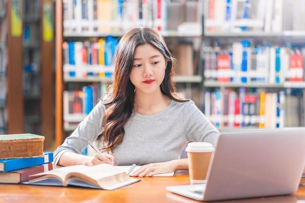 Azjatycka młoda studentka w zwykłym garniturze odrabiająca pracę domową i korzystająca z laptopa technologicznego w bibliotece