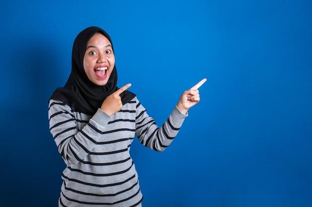 Azjatycka młoda szczęśliwa azjatycka muzułmańska studentka uśmiechnięta i wskazująca na prezentację czegoś na boku