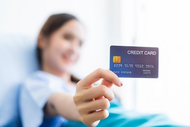 Azjatycka młoda żeńska cierpliwa smiley twarz abstrakcjonistyczna plama z ostrością na przedstawieniu trzyma kartę kredytową kłama na łóżku w izbowym szpitalu