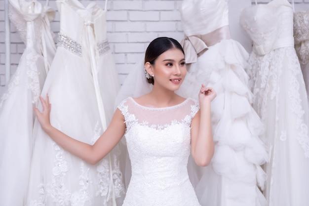 Azjatycka młodej kobiety panna młoda próbuje na ślubnej sukni przy nowożytnym ślubem