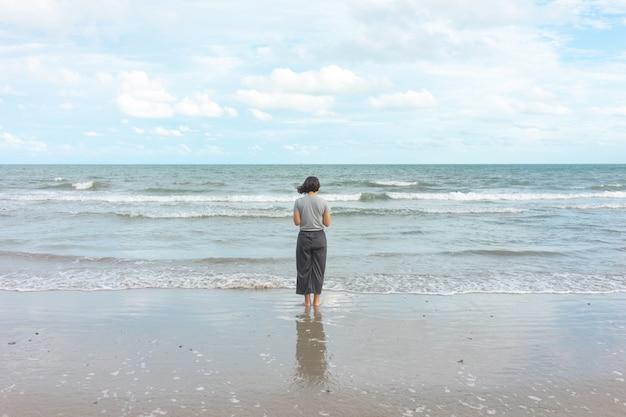 Azjatycka młodej kobiety pozycja stawia czoło morze. czuję się naprawdę samotny, z rozpaczliwym morzem