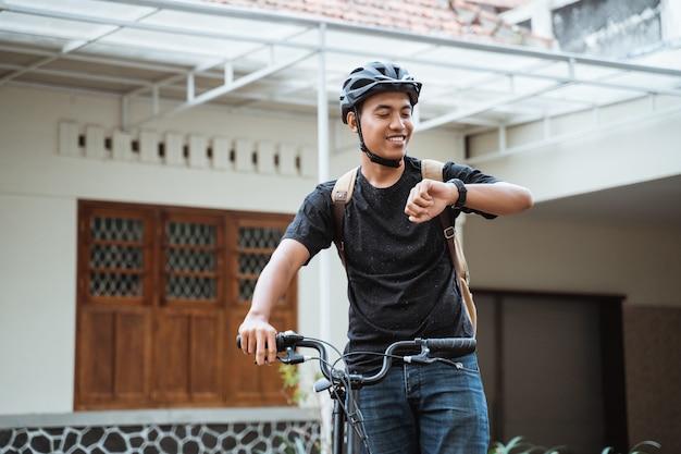 Azjatycka młody człowiek pozycja z falcowanie rowerem podczas gdy patrzejący jej zegarek