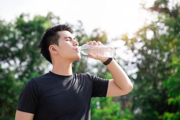 Azjatycka młody człowiek woda pitna po jogging