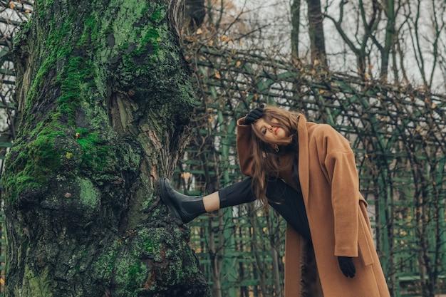 Azjatycka modelka pozuje w jesiennym stroju w ogrodzie letnim w sankt petersburgu.