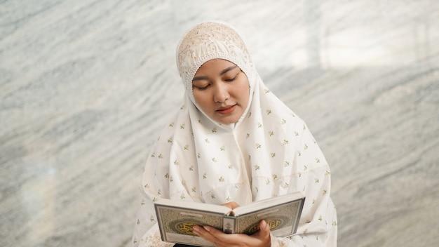 Azjatycka muzułmanka czytająca koran w meczecie