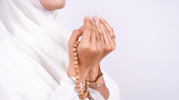 Azjatycka muzułmanka modli się na białym tle