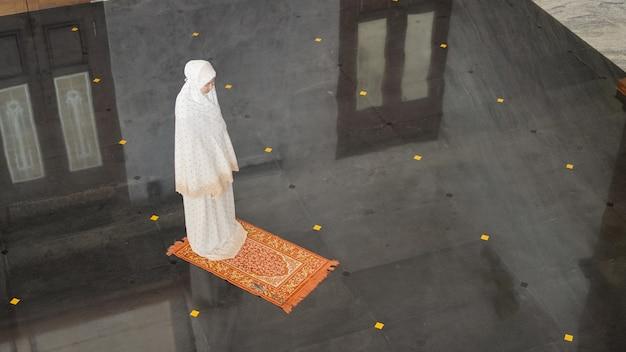 Azjatycka muzułmanka modli się samotnie bez imama w meczecie