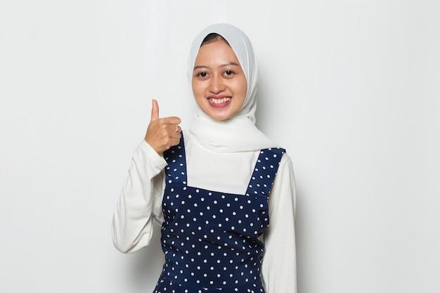 Azjatycka muzułmanka nosząca hidżab z kciukami w górę na białym tle