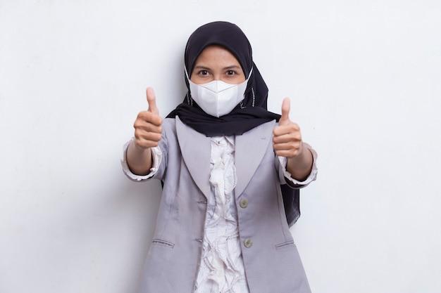 Azjatycka muzułmanka nosząca medyczną maskę do ochrony przed wirusem koronowym covid19 pozuje na białym