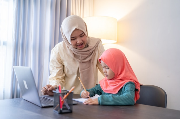 Azjatycka muzułmanka pomaga córce uczyć się podczas wieczornych zajęć w domu