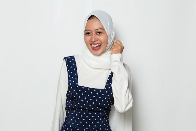 Azjatycka muzułmanka szczęśliwa i podekscytowana świętuje zwycięstwo, wyrażając wielką energię mocy sukcesu big