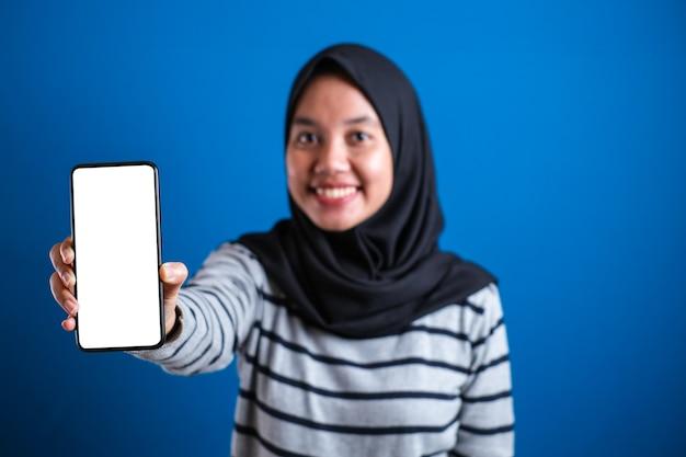 Azjatycka muzułmanka uśmiecha się do kamery i pokazuje makiety swojego smartfona