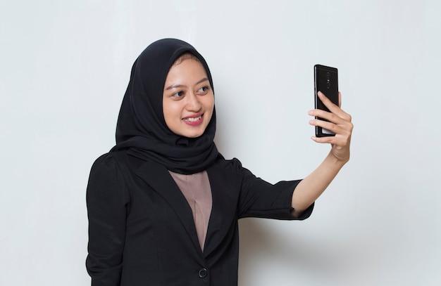 Azjatycka muzułmanka w hidżabie z telefonem komórkowym robi selfie