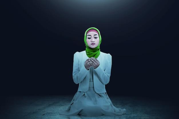 Azjatycka muzułmanka w welonie siedzi z podniesionymi rękami i modląc się