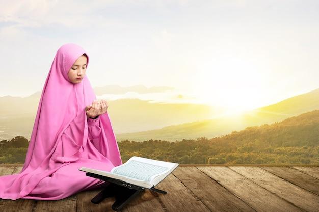 Azjatycka muzułmanka w welonie siedzi z podniesionymi rękami i modli się na drewnianej podłodze