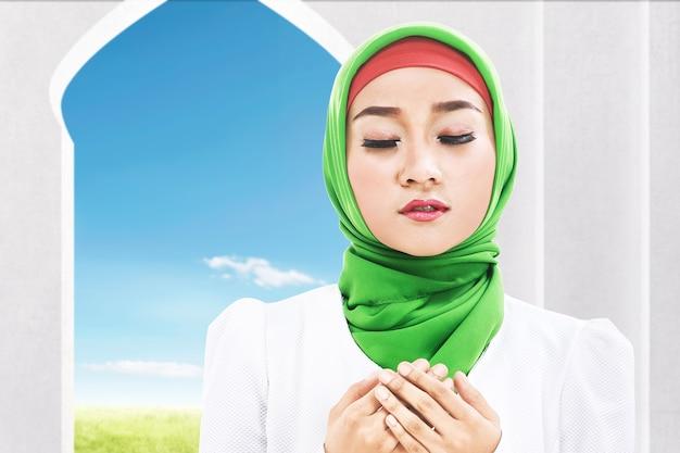 Azjatycka muzułmanka w welonie siedzi z podniesionymi rękami i modli się na meczecie