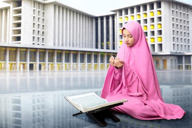 Azjatycka muzułmanka w welonie siedzi z podniesionymi rękami i modli się z meczetem