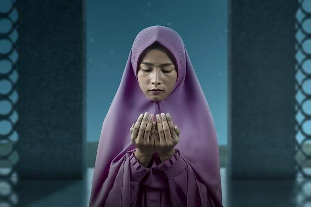 Azjatycka muzułmanka w welonie stojąc z podniesionymi rękami i modląc się na meczecie