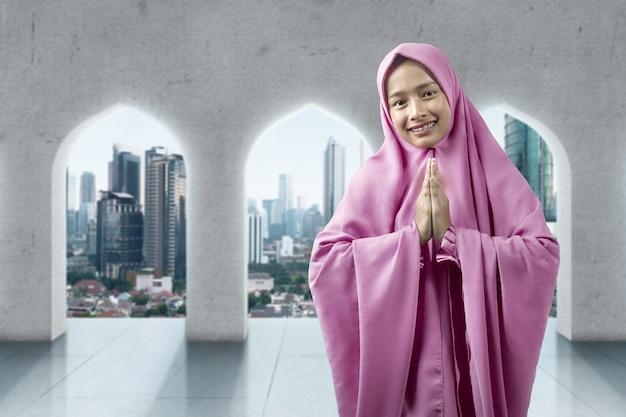 Azjatycka muzułmanka w welonie z pozdrowieniami na meczecie