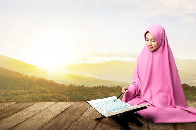 Azjatycka muzułmanka w zasłonie siedzi i czyta koran na drewnianej podłodze