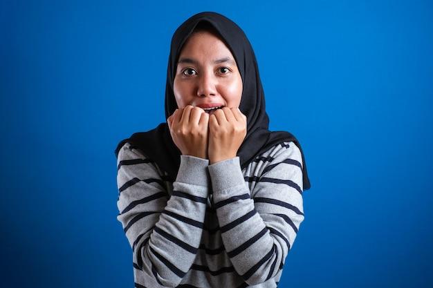 Azjatycka muzułmanka wygląda na przestraszoną obgryzając paznokcie na niebieskim tle