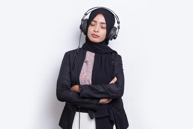 Azjatycka muzułmanka z hidżabu słuchająca muzyki na słuchawkach na białym tle