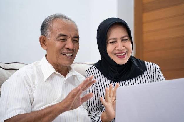 Azjatycka muzułmańska dojrzała para używa laptop