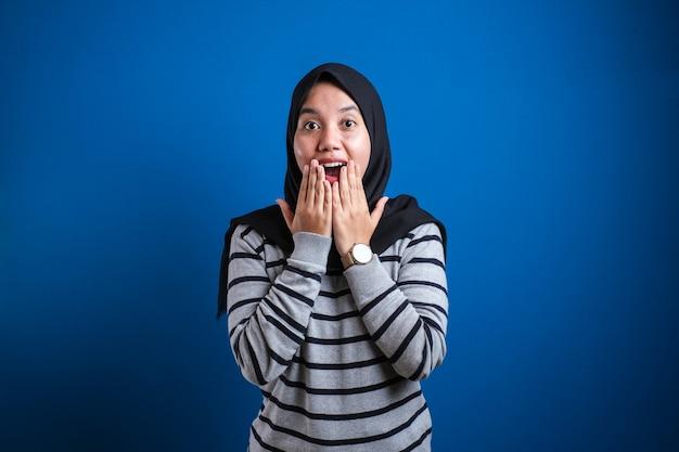 Azjatycka muzułmańska dziewczyna w hidżabie pokazuje zdziwioną lub zszokowaną minę z otwartymi ustami, z bliska wyraz twarzy na niebieskim tle