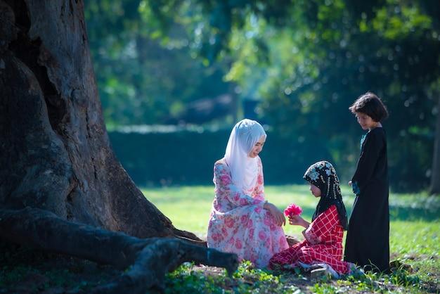 Azjatycka muzułmańska dziewczyna z rodziną mieszkającą i odpoczywającą pod drzewem na wakacjach. w ich domu o poranku pięknie świeci słońce.