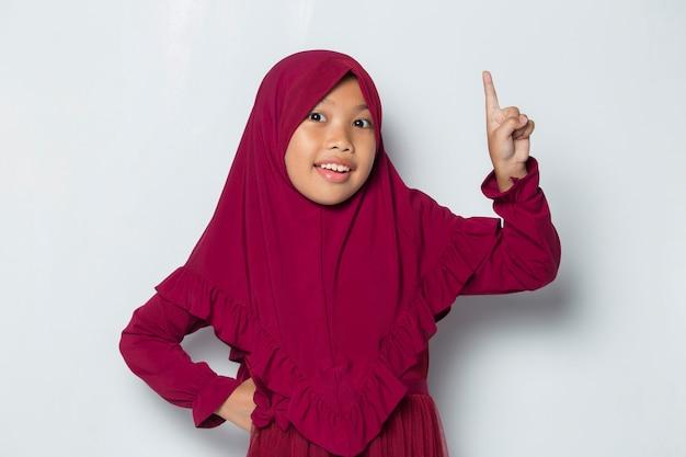 Azjatycka muzułmańska dziewczynka myśli, że pomysł na białym tle