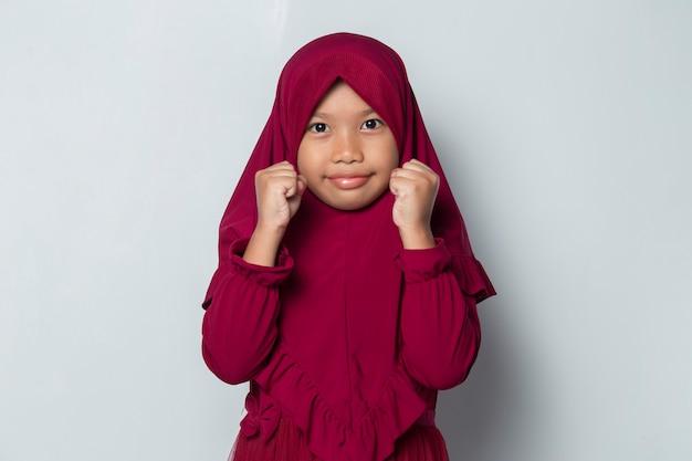 Azjatycka muzułmańska dziewczynka szczęśliwa i podekscytowana świętuje zwycięstwo, wyrażając wielki sukces