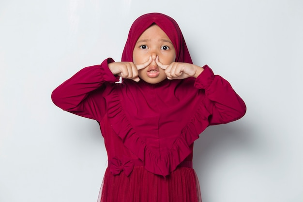 Azjatycka muzułmańska dziewczynka trzymająca nos z powodu nieprzyjemnego zapachu