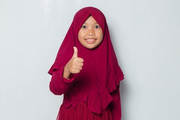 Azjatycka muzułmańska dziewczynka ubrana w hidżab z gestem ok gestem tumb up