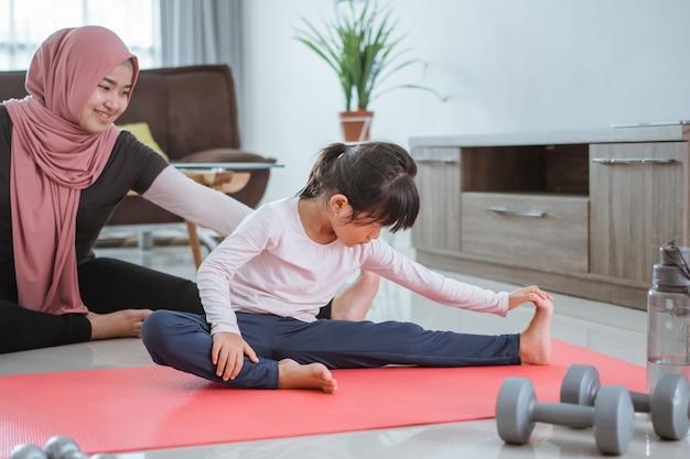 Azjatycka muzułmańska kobieta i córka robi ćwiczenia i sport w domu podczas samoizolacji