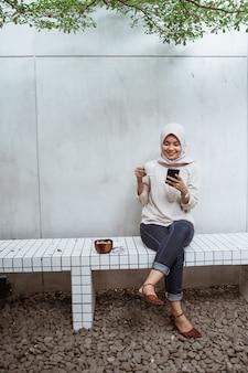 Azjatycka muzułmańska kobieta ono cieszy się przy kawiarnią