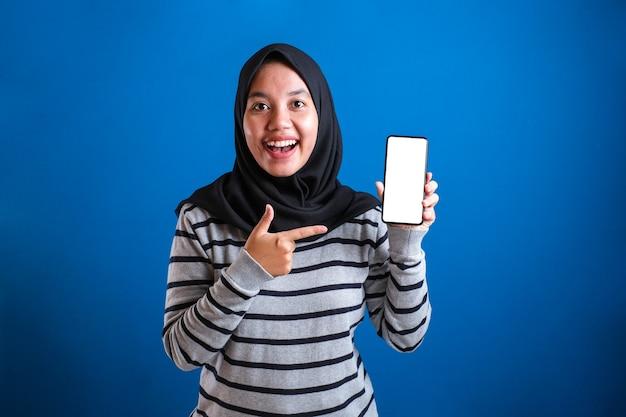 Azjatycka muzułmańska kobieta patrząca na kamerę, uśmiechająca się pokazująca i wskazująca swój inteligentny telefon