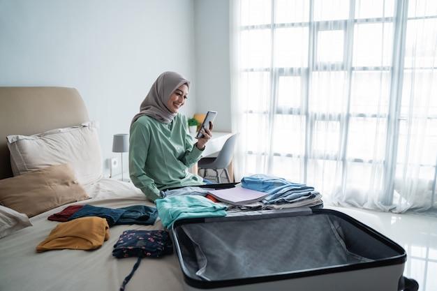 Azjatycka muzułmańska kobieta patrzeje odjazd rozkładów przez telefon komórkowy