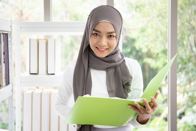 Azjatycka muzułmańska kobieta pisze książce w jej biurze