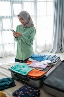 Azjatycka muzułmańska kobieta używa jej telefon komórkowego z pełną walizką