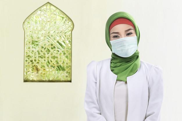 Azjatycka muzułmańska kobieta w przesłonie i będący ubranym maskę przeciw grypie