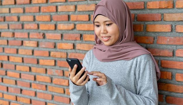 Azjatycka muzułmańska kobiety mienia smartphone robić zakupy online