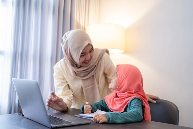 Azjatycka muzułmańska matka pomaga córce uczyć się online za pomocą laptopa, ucząc się w domu