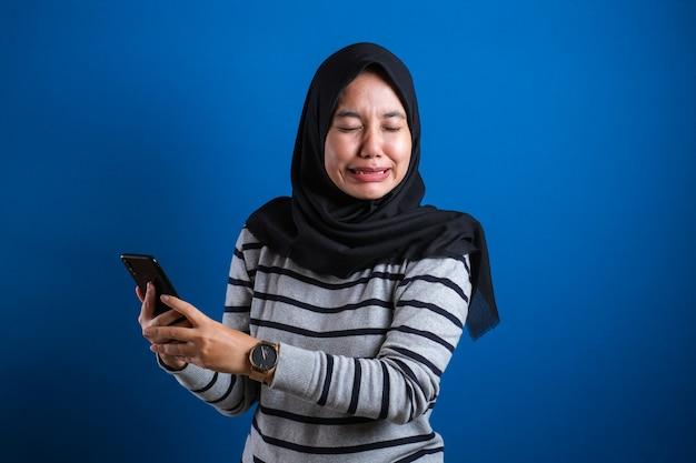 Azjatycka muzułmańska nastolatka płacze smutno, gdy odbiera telefonowi złe wiadomości na niebieskim tle